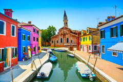 Ορόσημο της Βενετίας, κανάλι νησιών Burano, ζωηρόχρωμα σπίτια, εκκλησία και βάρκες, Ιταλία Στοκ Φωτογραφία
