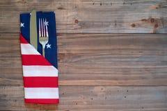 4ος επιτραπέζιας θέσης πικ-νίκ Ιουλίου της αγροτικής που θέτει με την πετσέτα ασημικών και αμερικανικών σημαιών με το υπόβαθρο τω στοκ εικόνα