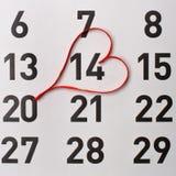 14ος της ημερολογιακής υπενθύμισης Φεβρουαρίου με μια κόκκινη καρδιά σατέν Στοκ φωτογραφίες με δικαίωμα ελεύθερης χρήσης