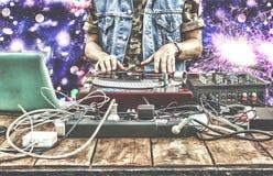 9ος του Μαρτίου Κόσμος ημέρα DJ Παίζοντας μουσική του DJ στην κινηματογράφηση σε πρώτο πλάνο αναμικτών DJ στο μακρινό σε ένα νυχτ Στοκ Εικόνα