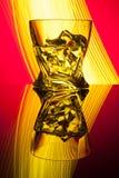 Ουίσκυ κοκτέιλ ένα γυαλί με τον πάγο κομματιών της αντανάκλασης κομμάτων μια έννοια των κίτρινων ελαφριών αποτελεσμάτων κλεψυδρών Στοκ Φωτογραφία