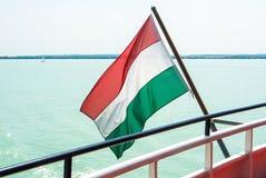 Ουγγρική σημαία στο κρουαζιερόπλοιο με το φωτεινό ανοικτό μπλε νερό ο Στοκ Φωτογραφία