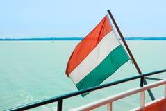 Ουγγρική σημαία στο κρουαζιερόπλοιο με το φωτεινό ανοικτό μπλε νερό ο Στοκ Εικόνες