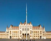 Ουγγρικό κτήριο Εθνικής Βουλής στη Βουδαπέστη με το τεράστιο κοντάρι σημαίας κοντά σε το είσοδος αριστερών πλευρών ` s, Ουγγαρία Στοκ Εικόνες