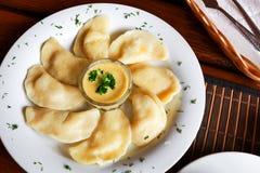 Ουκρανικό και ρωσικό vareniki πιάτων με τις πολτοποιηίδες πατάτες και ξινή σάλτσα κρέμας και μανιταριών στο άσπρο πιάτο κλείστε ε Στοκ Φωτογραφία