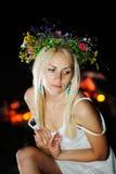 Ουκρανικό κορίτσι με ένα στεφάνι των λουλουδιών στο κεφάλι της ενάντια σε ένα BA Στοκ Εικόνες
