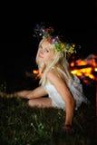 Ουκρανικό κορίτσι με ένα στεφάνι των λουλουδιών στο κεφάλι της ενάντια σε ένα BA Στοκ εικόνα με δικαίωμα ελεύθερης χρήσης