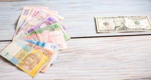 Ουκρανικό hryvnia και αμερικανικά δολάρια σε ένα ξύλινο υπόβαθρο Στοκ εικόνες με δικαίωμα ελεύθερης χρήσης