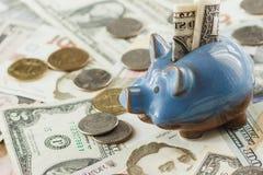 Ουκρανικό hryvnia και αμερικανικά δολάρια ` s με μια piggy τράπεζα Στοκ Εικόνα