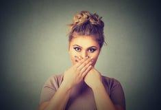 Ουπς! Έκπληκτη φοβησμένη γυναίκα που καλύπτει το στόμα με τα χέρια και που κοιτάζει επίμονα στη κάμερα Στοκ φωτογραφία με δικαίωμα ελεύθερης χρήσης