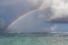 Ουράνιο τόξο, βροχή και σύννεφα πέρα από τον όμορφο όρμο με το τυρκουάζ νερό στη Γουαδελούπη, καραϊβική Στοκ φωτογραφία με δικαίωμα ελεύθερης χρήσης