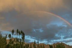 Ουράνιο τόξο στα βουνά: μεταξύ των χρυσών σύννεφων στον ουρανό μετά από τη βροχή είναι μια τεράστια χρωματισμένη αψίδα πέρα από τ Στοκ Εικόνες
