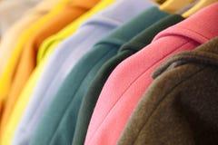 ουράνιο τόξο χρωμάτων Η επιλογή των μοντέρνων παλτών στις κρεμάστρες στο κατάστημα Στοκ Εικόνα