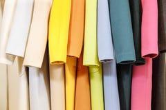 ουράνιο τόξο χρωμάτων Η επιλογή των μοντέρνων παλτών στις κρεμάστρες στο κατάστημα Στοκ Φωτογραφία