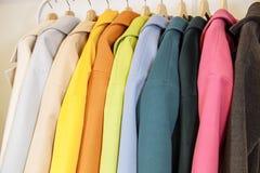 ουράνιο τόξο χρωμάτων Η επιλογή των μοντέρνων παλτών στις κρεμάστρες στο κατάστημα Στοκ Εικόνες