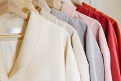 ουράνιο τόξο χρωμάτων Η επιλογή των μοντέρνων παλτών στις κρεμάστρες στο κατάστημα Στοκ εικόνες με δικαίωμα ελεύθερης χρήσης