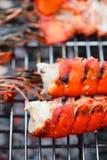 Ουρές αστακών που ψήνονται στη σχάρα BBQ με τη φλόγα Στοκ Φωτογραφία