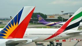 Ουρές του ταϊλανδικού airbus 340-600 εναέριων διαδρόμων, των εμιράτων Boeing 777-300ER και του airbus 330 αερογραμμών των Φιλιππι Στοκ εικόνες με δικαίωμα ελεύθερης χρήσης