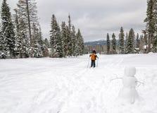 Ουρανοί νέων κοριτσιών μετά από έναν χιονάνθρωπο σε εκείνο το ίχνος Στοκ Εικόνες