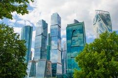 Ουρανοξύστες ενάντια στον ουρανό με τα σύννεφα στοκ εικόνες