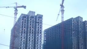 ουρανοξύστες ουρανού ανώτερων αξιωμάτων οικοδόμησης κτηρίων ανασκόπησης ύψους Εργοτάξιο με τους γερανούς και κτήρια απόθεμα βίντεο