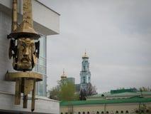 ουρανοξύστες της Ρωσία&sigma Θεατρική μάσκα στο μέτωπο του θεάτρου ` του νέου θεατή ` με τη Ορθόδοξη Εκκλησία πίσω από το Στοκ Φωτογραφία