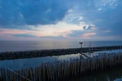 Ουρανός βραδιού και σειρές των ραβδιών μπαμπού στη θάλασσα κοντά στη λάρνακα Matchanu, Phanthai Norasing, περιοχή Mueang Samut Sa Στοκ Φωτογραφίες