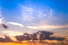 ουρανός ηλιοβασιλέματος με τα κίτρινες και λάμποντας σύννεφα κόκκινου φωτός και την πλάτη ουρανού Στοκ Εικόνες