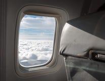 Ουρανός που βλέπει νεφελώδης μέσω του παραθύρου ενός αεροπλάνου Στοκ Φωτογραφίες