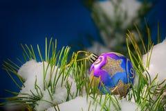 ουρανός santa του Klaus παγετού Χριστουγέννων καρτών τσαντών Σφαίρα Χριστουγέννων σε έναν χιονώδη κομψό κλάδο Στοκ Εικόνα