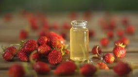 Ουσία της άγριας φράουλας στον πίνακα στο όμορφο βάζο γυαλιού απόθεμα βίντεο