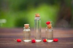 Ουσία της άγριας φράουλας στον πίνακα στο όμορφο μπουκάλι γυαλιού Στοκ Εικόνες