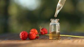 Ουσία της φράουλας στον πίνακα στο όμορφο βάζο γυαλιού φιλμ μικρού μήκους