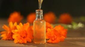 Ουσία των λουλουδιών calendula στον πίνακα στο όμορφο μπουκάλι γυαλιού φιλμ μικρού μήκους