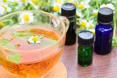 Ουσιαστικά πετρέλαια με ένα φλυτζάνι του τσαγιού και των λουλουδιών Στοκ εικόνα με δικαίωμα ελεύθερης χρήσης