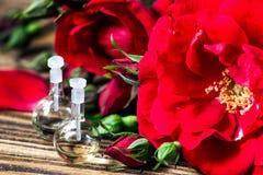 Ουσιαστικό πετρέλαιο στο μπουκάλι γυαλιού με τα κόκκινα ροδαλά λουλούδια και τα πέταλα στο ξύλινο υπόβαθρο επεξεργασία σαπουνιών  Στοκ εικόνα με δικαίωμα ελεύθερης χρήσης