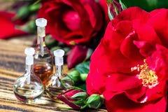 Ουσιαστικό πετρέλαιο στο μπουκάλι γυαλιού με τα κόκκινα ροδαλά λουλούδια και τα πέταλα στο ξύλινο υπόβαθρο επεξεργασία σαπουνιών  Στοκ Φωτογραφία