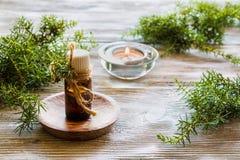 Ουσιαστικό πετρέλαιο ιουνιπέρων σε ένα μπουκάλι γυαλιού σε έναν ξύλινο πίνακα Στοκ Φωτογραφία