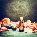 Ουσιαστικό πετρέλαιο τριαντάφυλλων στο μπουκάλι στο αγροτικό εκλεκτής ποιότητας υπόβαθρο, τοπ άποψη, θέση για το κείμενο Στοκ Εικόνα