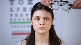 Οφθαλμολόγος που βάζει τη διόπτρα στο φοβησμένο θηλυκό ασθενή, που αναλύει την όραση απόθεμα βίντεο
