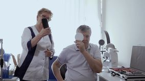 Οφθαλμολόγος που εξετάζει τα μάτια του ανώτερου ατόμου στην κλινική απόθεμα βίντεο
