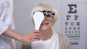 Οφθαλμολόγος που κλείνει την ανώτερη κυρία στο μάτι phoropter, που ελέγχει τη διόπτρα φακών απόθεμα βίντεο