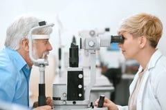 Οφθαλμολόγος που το υπομονετικό όραμα ` s με το ιατρικό εξοπλισμό Στοκ Εικόνες