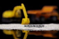 Οχήματα και άμμος κατασκευής παιχνιδιών με την κατοικία λέξης στις χάντρες που απεικονίζονται στοκ εικόνα