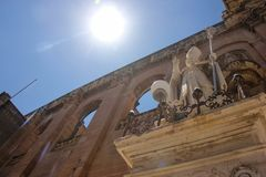 Ο Άγιος στην πρόσοψη της εκκλησίας του ST Publius ` δείχνει τον ήλιο με το δάχτυλό του στοκ φωτογραφία