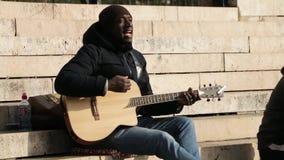 Ο άγνωστος μουσικός παίζει την κιθάρα και τραγουδά στην οδό απόθεμα βίντεο