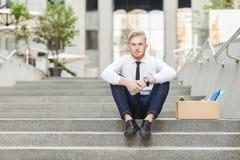 Ο άδικος εργαζόμενος πιπεροριζών κάθεται στο σκαλοπάτι και seriosly εξέταση τη κάμερα Στοκ Εικόνες
