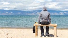 Ο άνδρας ή η γυναίκα κάθεται σε ένα hoodie στην παραλία υποστηρίξτε την όψη Χρονικό σφάλμα 4K απόθεμα βίντεο