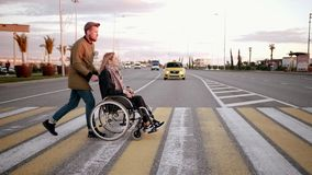 Ο άνδρας απομακρύνει τη με ειδικές ανάγκες γυναίκα στη μεταφορά πέρα από το για τους πεζούς πέρασμα στην πόλη απόθεμα βίντεο