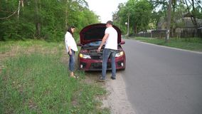 Ο άνδρας βοηθά τη γυναίκα με το σπασμένο αυτοκίνητό της στη μέση μιας επαρχίας απόθεμα βίντεο